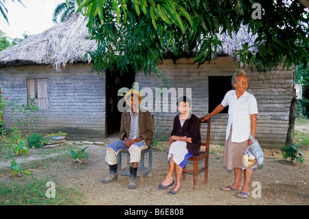 cuba holguin province locals sitting outside their traditional house in the countryside - Stock Photo