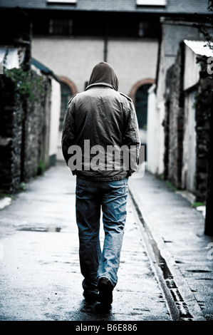 Young man wearing a hooded jacket alone and isolated walking down an alleyway in a city UK seen from behind walking - Stock Photo