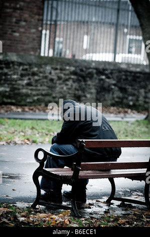 Young man wearing a hooded jacket depressed lonely alone and isolated sitting on a park bench UK - Stock Photo