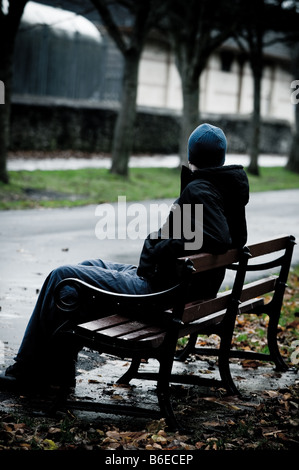 Young man wearing a hooded jacket alone and isolated sitting on a park bench - Stock Photo