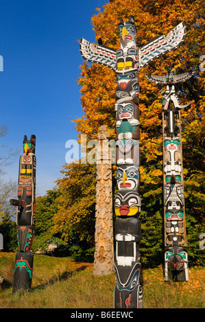 Totem poles aboriginal wood carving in Stanley Park Vancouver with raven and changing maple leaves in Autumn on - Stock Photo