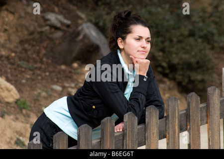 portrait sad looking young woman standing by fence - Stock Photo