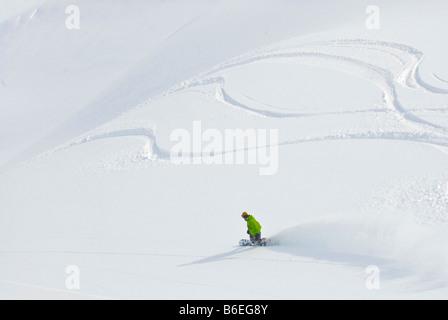 Lone snowboarder descending a fresh alpine bowl - Stock Photo