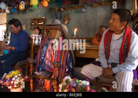 Maximon, a Maya saint attended by two men, in his temporal residence in Santiago Atitlan, Guatemala. - Stock Photo