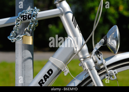 Bicycle chained to a post with a padlock - Stock Photo