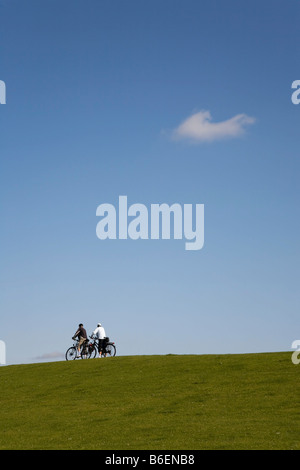 Bicycle tourists cycling on a North See Dyke in North Frisia or Nordfriesland, Schleswig-Holstein, Germany, Europe - Stock Photo