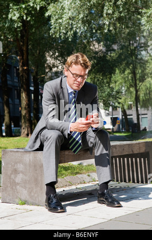 Businessman on bench with cellphone - Stock Photo