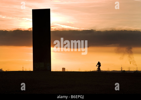 bicyclist and art work in backlight on Schurenbachhalde, an old mining dump, Germany, North Rhine-Westphalia, Ruhr - Stock Photo