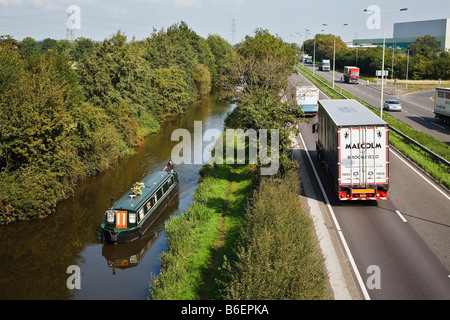 Busy traffic on the A38 contrasted with a narrowboat leisurely making its way along the Trent and Mersey Canal near - Stock Photo
