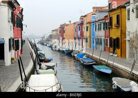 Canal lined with boats running between colorfully painted building facades in Burano, Venice, Venetia, Italy, Europe - Stock Photo