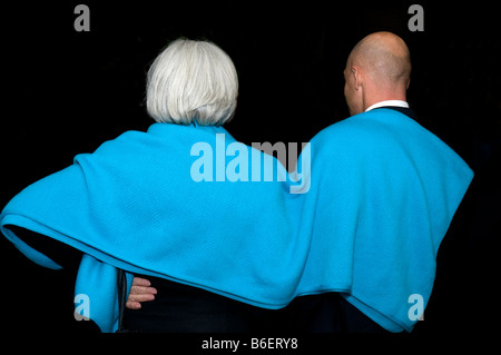 Rear view of man and woman with a blue blanket on shoulders