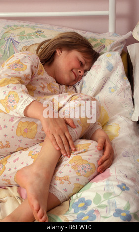 young girl in bed clutching her leg in pain - Stock Photo