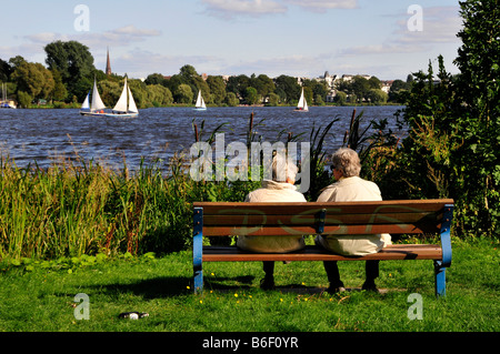 Two pensioners watching the sailboats on the outer Alster, Hamburg, Germany, Europe - Stock Photo