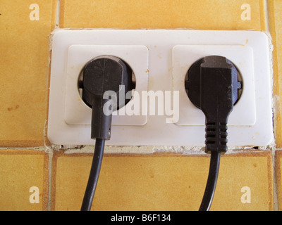 Two electrical plugs plugged into sockets in wall - Stock Photo