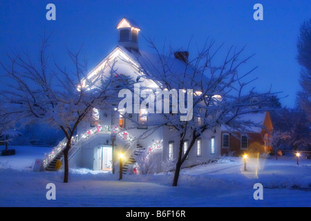 A quaint old pioneer Church surrounded by snowy trees at Christmas time in Pioneer Village State Park in Salt Lake - Stock Photo