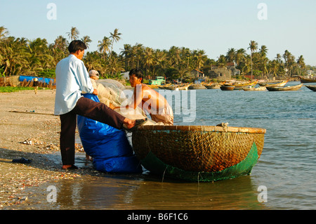 People in a traditional roundboat on the fishing beach of Mui Ne, Vietnam, Asia - Stock Photo