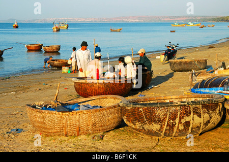 Fishermen in their traditional round boats in the fishing harbour of Mui Ne, Vietnam, Southeast Asia - Stock Photo