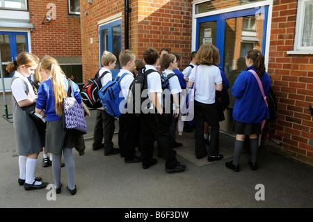 Primary school children wait in playground to enter their school to open - Stock Photo