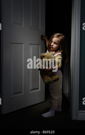 Little girl looking out of a room at night - Stock Photo