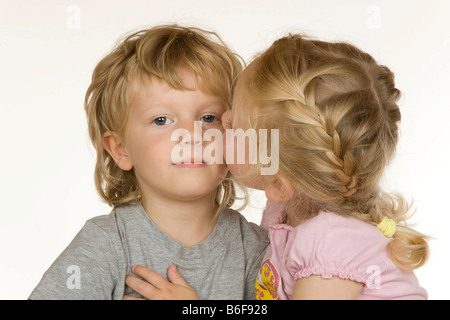 Girl, two years old, kisses boy, three years old, on the cheek - Stock Photo
