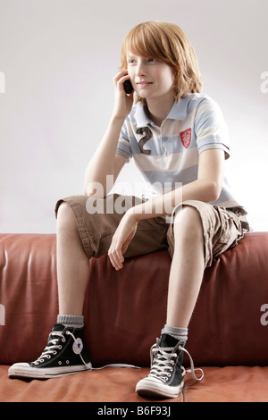 12 year-old boy, sitting on a sofa talking on the phone - Stock Photo