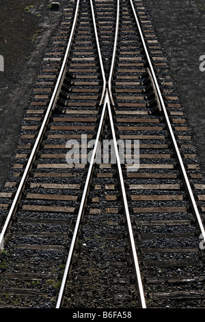 Railway tracks with a switch joining two tracks into one, view from above - Stock Photo