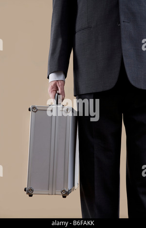 Hand of a businessman holding a metal case - Stock Photo