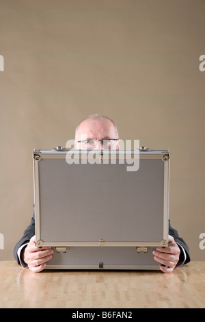 Businessman looking over a metal case - Stock Photo