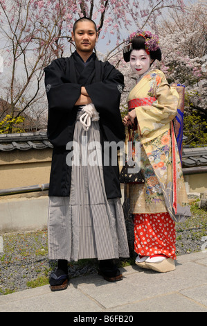 A Maiko, a trainee Geisha, and Japanese man wearing a Kimono, in front of cherry trees in bloom, Kyoto, Japan, Asia - Stock Photo
