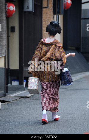 A Maiko, a trainee Geisha, walking in the Gion Quarter on her way to Odori, Kyoto, Japan, Asia - Stock Photo