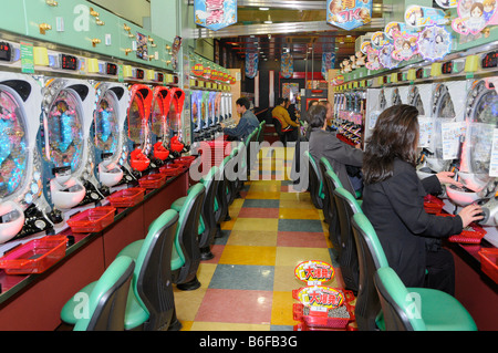 Japanese gambling on flipper game machines in a flipper gaming hall, Paschinko, in Kyoto, Japan, Asia - Stock Photo