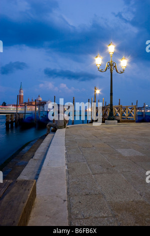 Two men talking by the Grand Canal, in the back San Giorgio Maggiore at dusk, Venice, Italy, Europe - Stock Photo