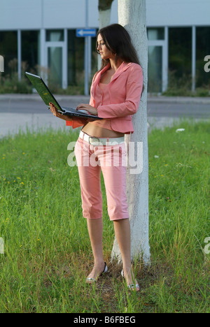 Young woman wearing a pink suit leaning against a white tree trunk while working on a laptop - Stock Photo