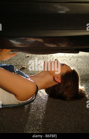Young woman in working clothes is lying under her car while fixing it