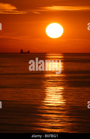 Freight ship on the North Sea in front of the setting sun, Germany, Europe - Stock Photo