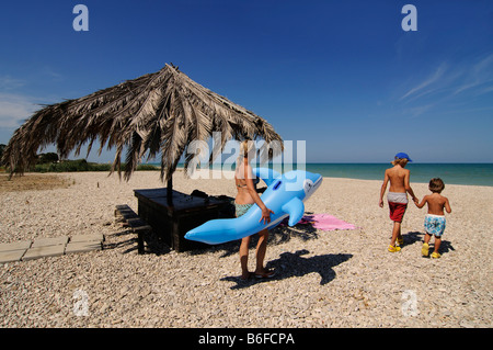 Mother with chilldren on the beach of Pineto, Abruzzi, Italy, Europe - Stock Photo