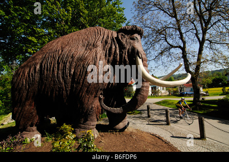 Woolly Mammoth figure, life size, overlooking racing cyclist in Siegsdorf, Chiemgau, Bavaria, Germany, Europe - Stock Photo