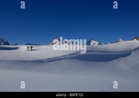 Back country skiers, freeriders, hiking over the Sandiger Boden ski area in front of the Zinalrothorn and Obergabelhorn - Stock Photo