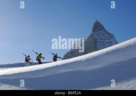 Back country skiers, freeriders, hiking over the Sandiger Boden ski area in front of the Matterhorn Mountain, Zermatt, - Stock Photo