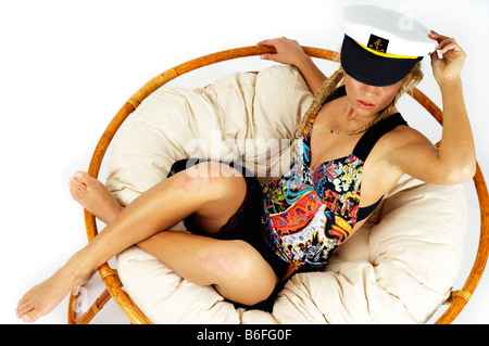 Young woman wearing swimsuit and seaman's cap, lying in a lounge chair - Stock Photo