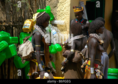 Black skinned Hamar people with white kauri mussel necklaces in front of green plastic canisters, market of Dimeka, - Stock Photo