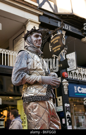 UK Cheshire Chester city centre at Christmas the silver man mime artist entertaining shoppers - Stock Photo