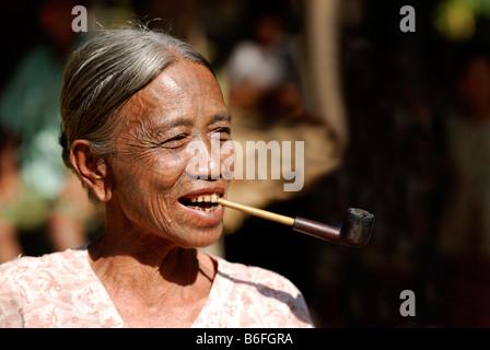 Smoking tattooed woman, so called spider women, Mrauk-U, Burma, also called Myanmar, Southeast Asia - Stock Photo