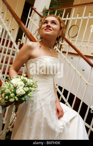 Smiling pretty bride walking downstairs with bouquet - Stock Photo