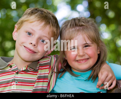 A girl, four years old, and a boy, six years old, arm in arm - Stock Photo