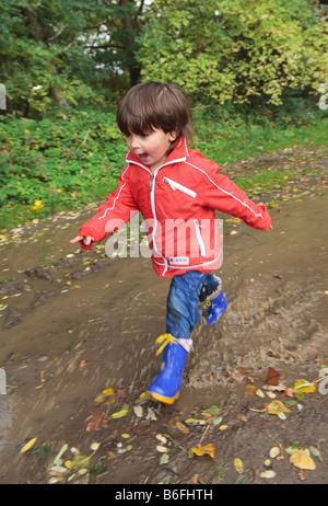 Child wearing rubber boots walking through puddles, Niederwerth, Rhineland-Palatinate, Germany, Europe - Stock Photo