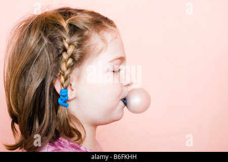 Little girl, 9 years old, blowing a gum bubble - Stock Photo