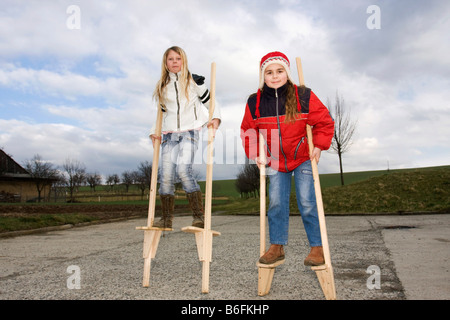 Little girls, 11 and 10 years old, on stilts, outside - Stock Photo