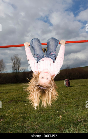 Fair-haired little girl, 6 years, playing on the cross-bar - Stock Photo