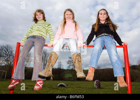 Three little girls sitting on a cross-bar, 9, 11 and 9 years - Stock Photo